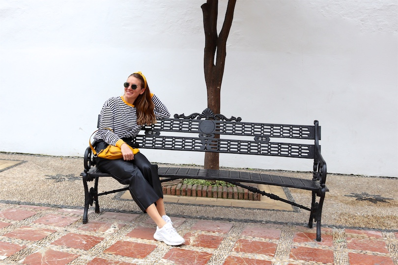 Yellow Belt Bag. Fashion and Style Blog Girl from Heartfelt Hunt. Girl with blonde hair and yellow headband wearing a yellow belt bag, striped top, faux leather culotte, Ray-Ban sunglasses and chunky sneakers.