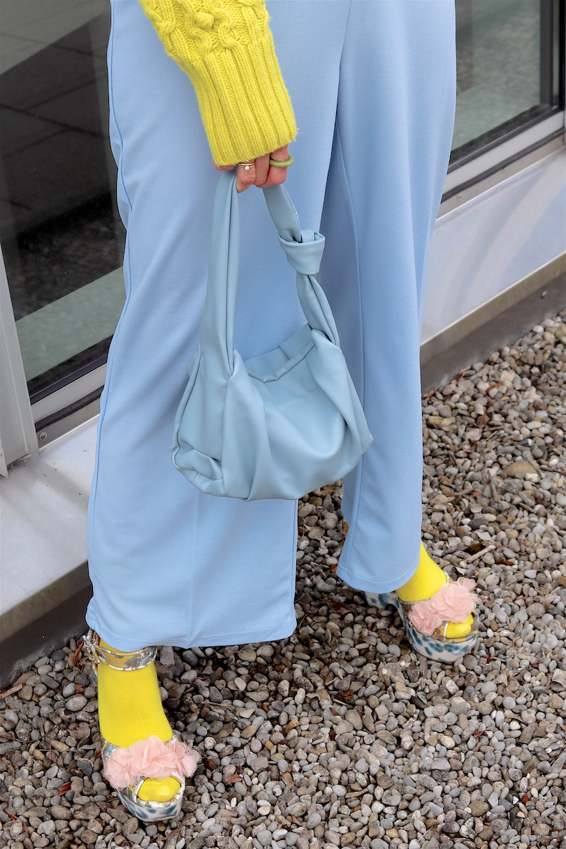 Yellow Blue. Fashion and Style Blog Girl from Heartfelt Hunt. Girl with blonde hair wearing a yellow & blue outfit with a yellow sweater, blue pants, yellow socks, blue knotted bag and blue heels.
