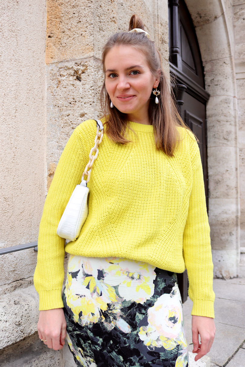 Yellow Flowers. Fashion Blogger Girl by Style Blog Heartfelt Hunt. Girl with blond half-up half-down messy bun and scrunchie wearing a yellow sweater, dress with yellow flowers, eye earrings, white bag and white boots.