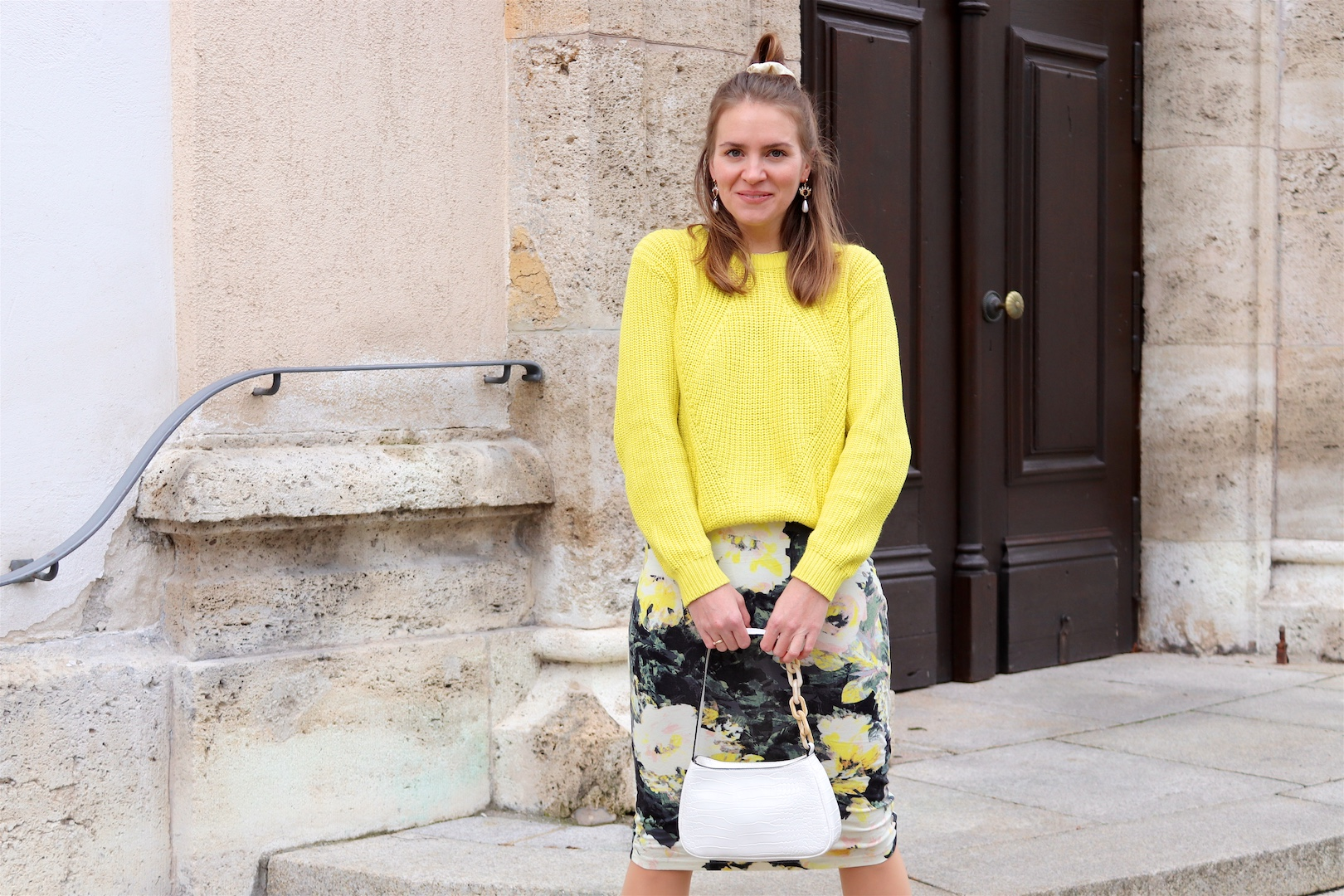 Yellow Flowers. Fashion and Style Blog Girl from Heartfelt Hunt. Girl with blonde half-up half-down messy bun and scrunchie wearing a yellow sweater, dress with yellow flowers, eye earrings, white bag and white boots.