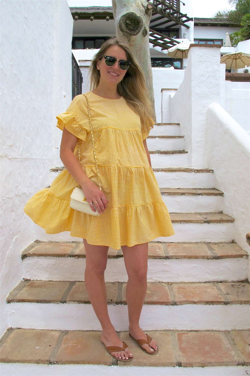 Yellow Gingham. Fashion Blogger Girl by Style Blog Heartfelt Hunt. Girl with blond, long hair wearing a yellow gingham dress, vintage Chanel bag, Ray-Ban sunglasses and sandals.
