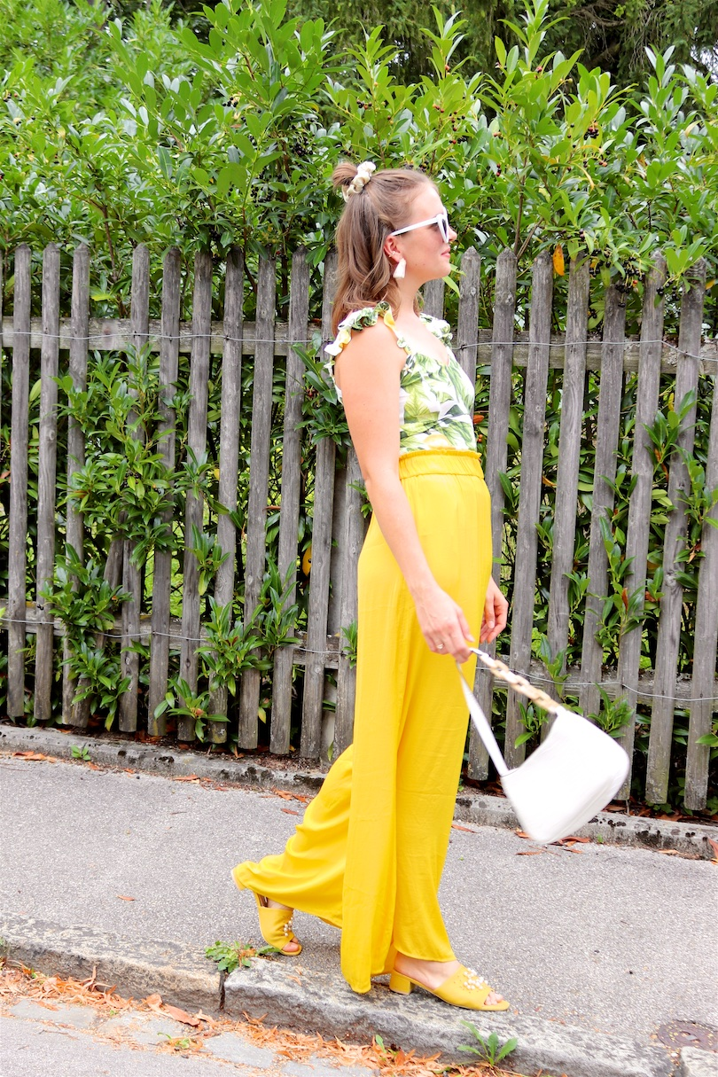 Yellow Lemon Print. Fashion and Style Blog Girl from Heartfelt Hunt. Girl with blonde half-up half-down messy bun and scrunchie wearing a yellow pants, lemon print top, heart-shaped sunglasses, white bag and yellow sandals.