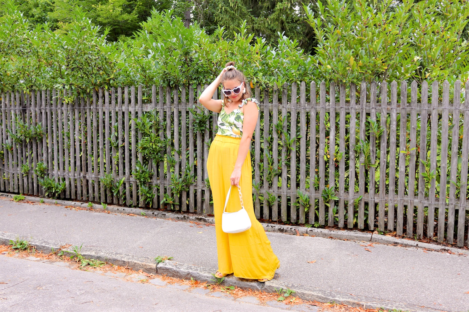 Yellow Lemon Print. Fashion Blogger Girl by Style Blog Heartfelt Hunt. Girl with blond half-up half-down messy bun and scrunchie wearing a yellow pants, lemon print top, heart-shaped sunglasses, white bag and yellow sandals.