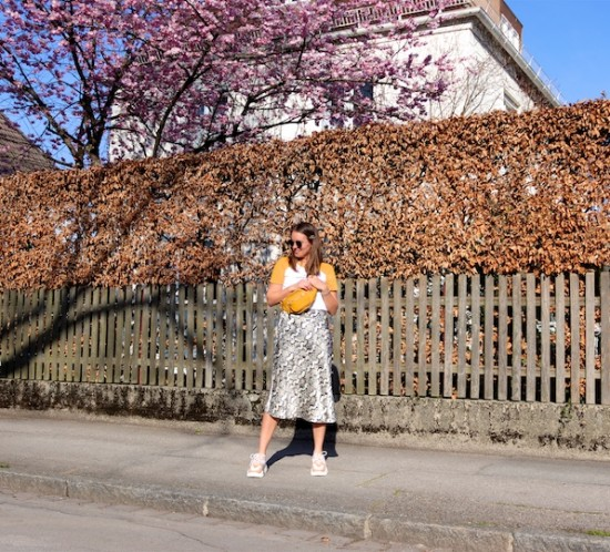 Yellow Spring. Fashion Blogger Girl by Style Blog Heartfelt Hunt. Girl with blond hair wearing a yellow T-shirt, snake print skirt, Ray-Ban sunglasses, hair clip, yellow belt bag and chunky sneakers.