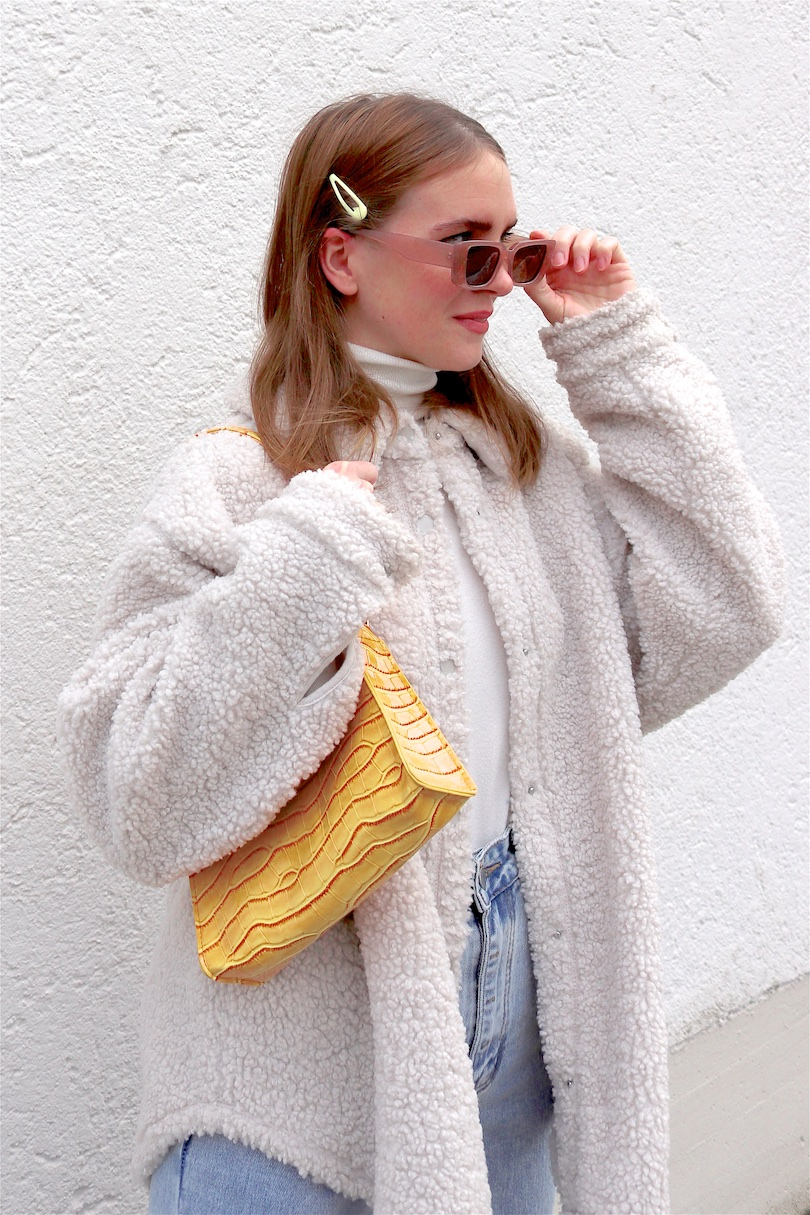 Yellow Spring Vibes. Fashion and Style Blog Girl from Heartfelt Hunt. Girl with blonde hair wearing a yellow bag, shacket, turtleneck sweater, wide leg jeans, yellow 90s bag and chunky sneakers.