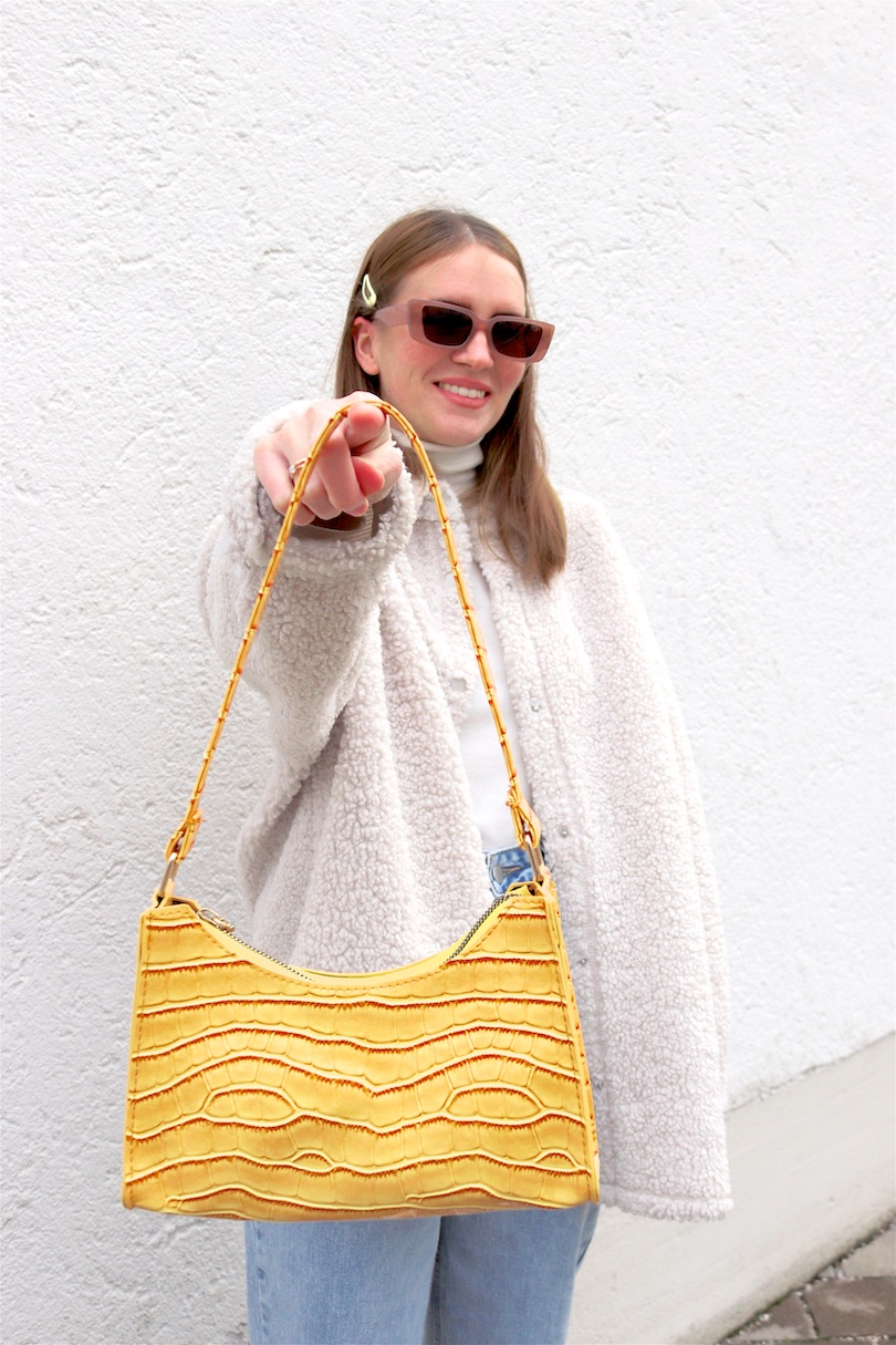 Yellow Spring Vibes. Fashion Blogger Girl by Style Blog Heartfelt Hunt. Girl with blond hair wearing a yellow bag, shacket, turtleneck sweater, wide leg jeans, yellow 90s bag and chunky sneakers.