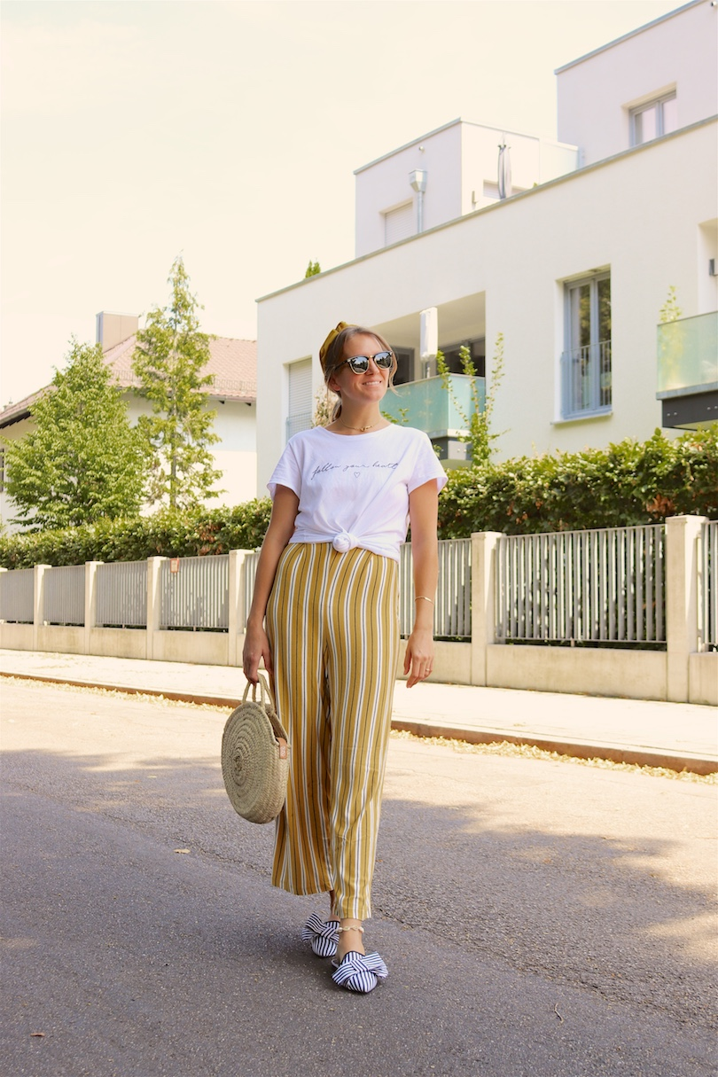 Yellow Stripes. Fashion Blogger Girl by Style Blog Heartfelt Hunt. Girl with blond, low messy bun and yellow headband wearing a jumpsuit with yellow stripes, white T-shirt, Ray-Ban sunglasses, round straw bag and striped mules.