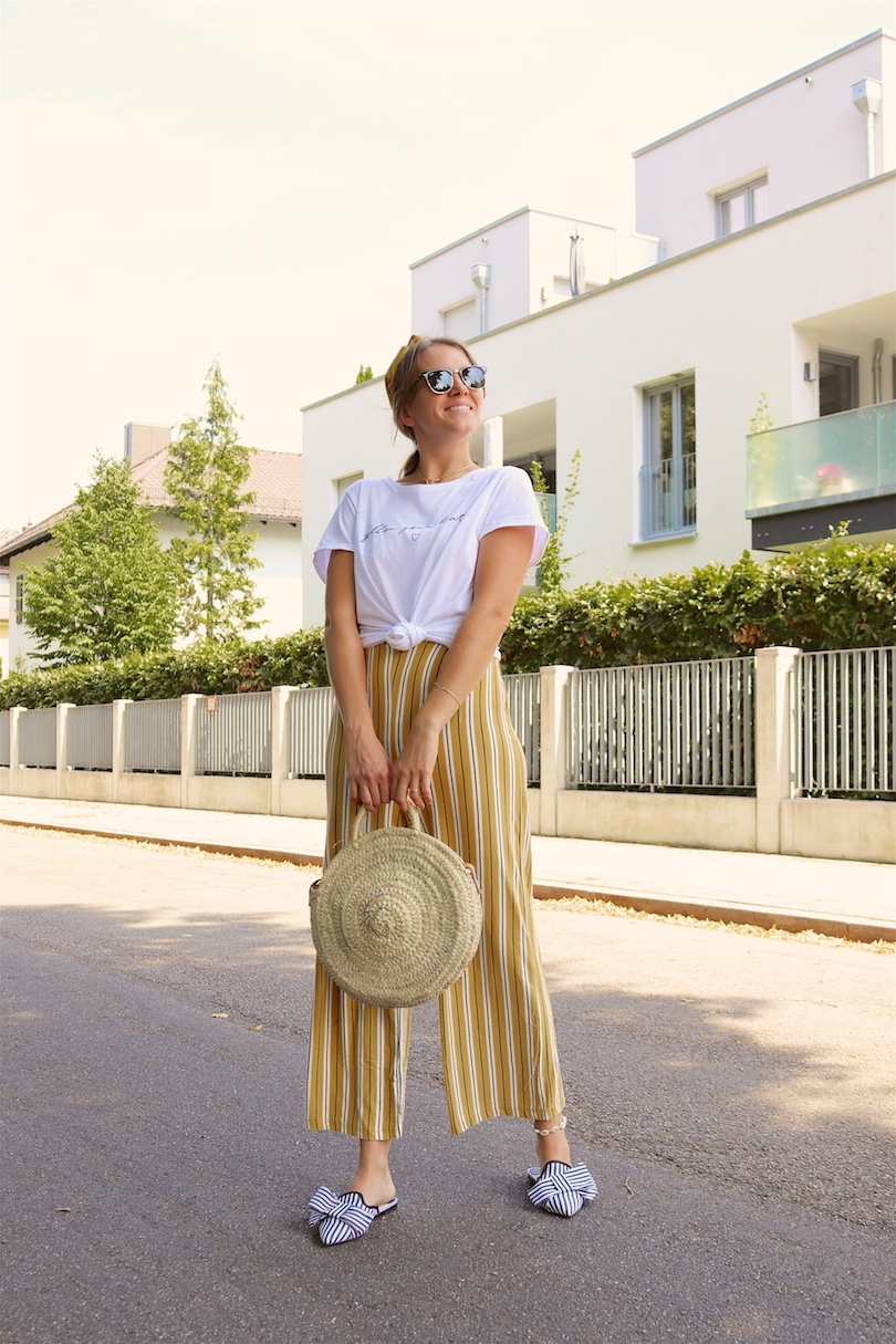 Yellow Stripes. Fashion and Style Blog Girl from Heartfelt Hunt. Girl with blonde, low messy bun and yellow headband wearing a jumpsuit with yellow stripes, white T-shirt, Ray-Ban sunglasses, round straw bag and striped mules.