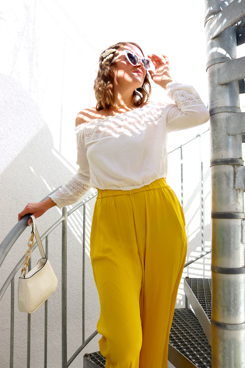 Yellow Summer Vibes. Fashion and Style Blog Girl from Heartfelt Hunt. Girl with blonde, loose waves and pearl hair clips wearing a yellow summer pants, white off-shoulder top, heart-shaped sunglasses, white bag and white mules.