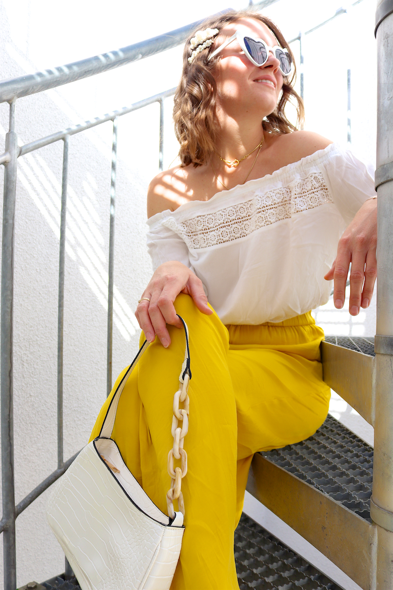 Yellow Summer Vibes. Fashion Blogger Girl by Style Blog Heartfelt Hunt. Girl with blond, loose waves and pearl hair clips wearing a yellow summer pants, white off-shoulder top, heart-shaped sunglasses, white bag and white mules.