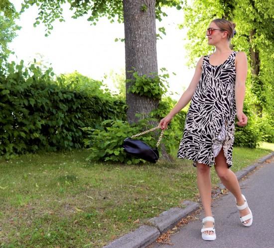 Zebra Print Dress. Fashion Blogger Girl by Style Blog Heartfelt Hunt. Girl with blond hair wearing a zebra print dress, orange sunglasses, black pouch bag and chunky sandals.