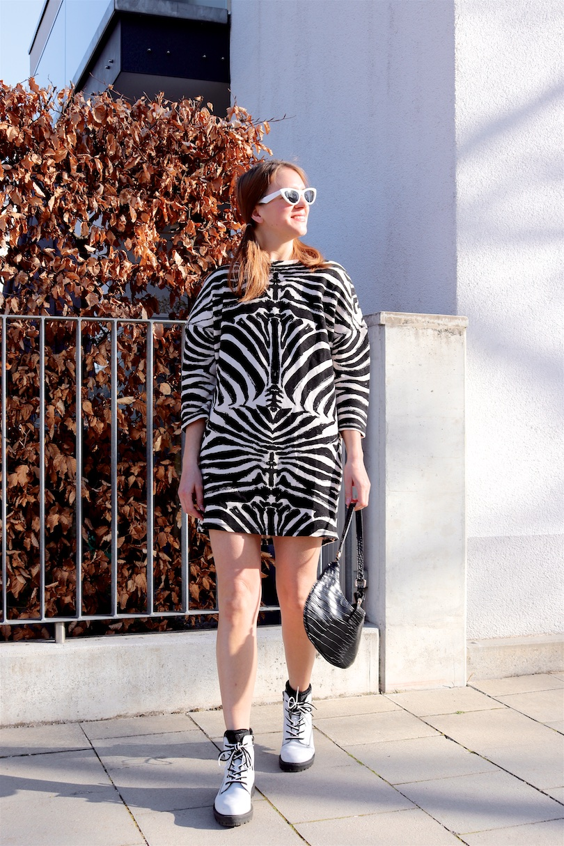 Zebra Print Trend. Fashion and Style Blog Girl from Heartfelt Hunt. Girl with blonde hair wearing a zebra print dress, white slim sunglasses, 90s bag and white boots.